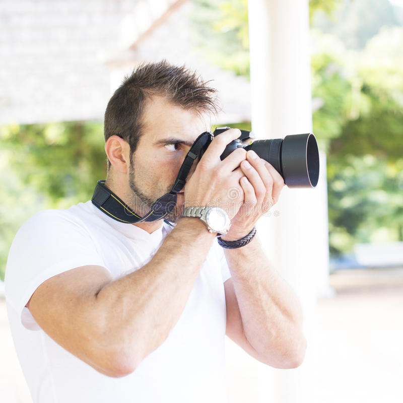 Download Фотограф используя профессиональную камеру. Стоковое Фото - изображение насчитывающей посмотрите, актеров: 33727528