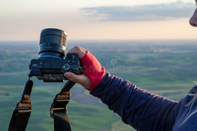 Фотограф молодой женщины показывает ее камеру Sony A6500 Mirrorless SLR, используя автоматическую установку стоковые изображения rf