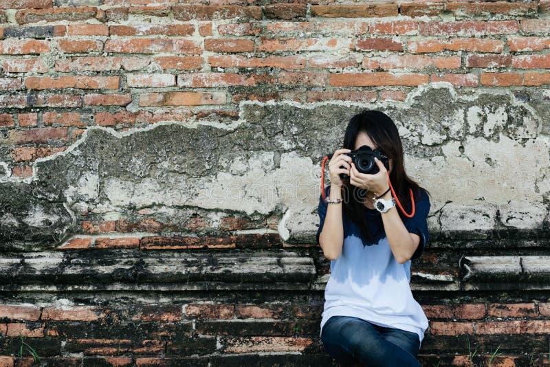 Фотограф молодой женщины портрета вид спереди держа камеру и стоковые фотографии rf