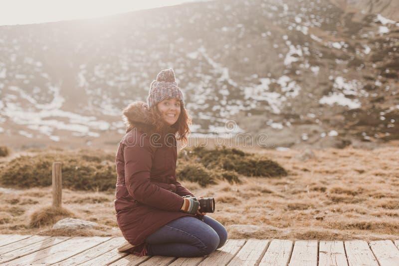 Фотограф молодой женщины принимая фото на горный пик и усмехаясь на заходе солнца стоковые фотографии rf