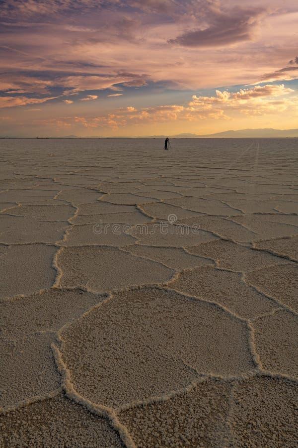 Фотограф на квартирах соли Bonneville с драматическим заходом солнца стоковое изображение rf