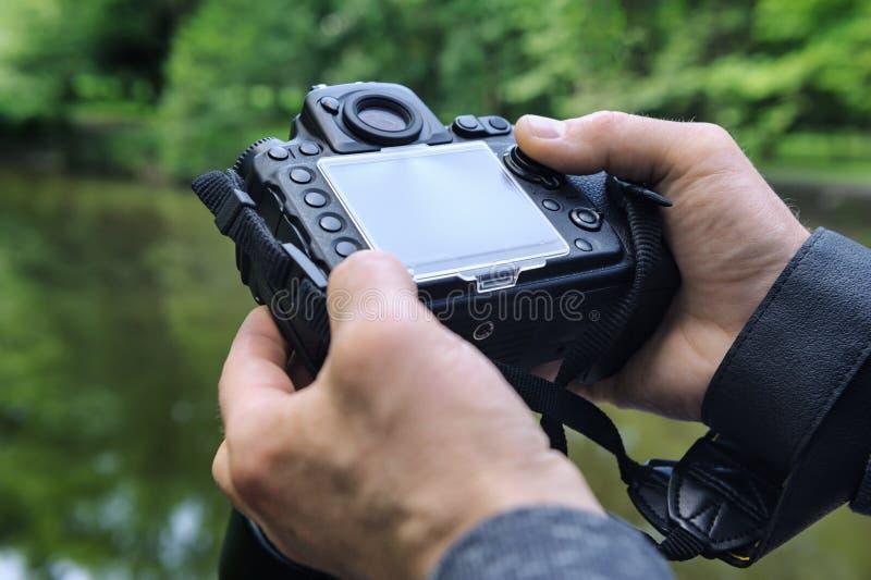 Фотограф регулирует камеру стоковые изображения