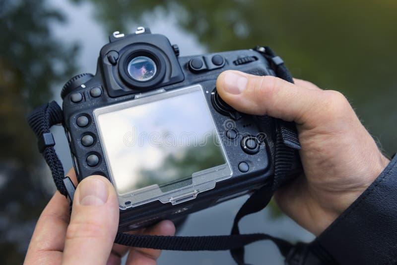 Фотограф регулирует камеру стоковые фото