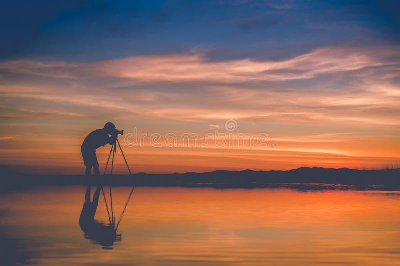 Фотограф силуэта принимает фото красивый seascape на заход солнца стоковая фотография rf