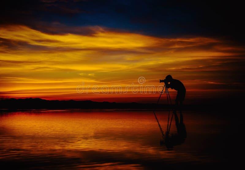 Фотограф силуэта принимает фото красивый seascape на заход солнца стоковые фотографии rf