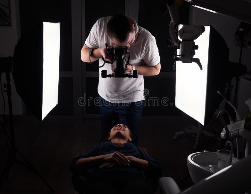 Фотограф снимает модель которая лежит на зубоврачебном кресле, фото студии стоковая фотография