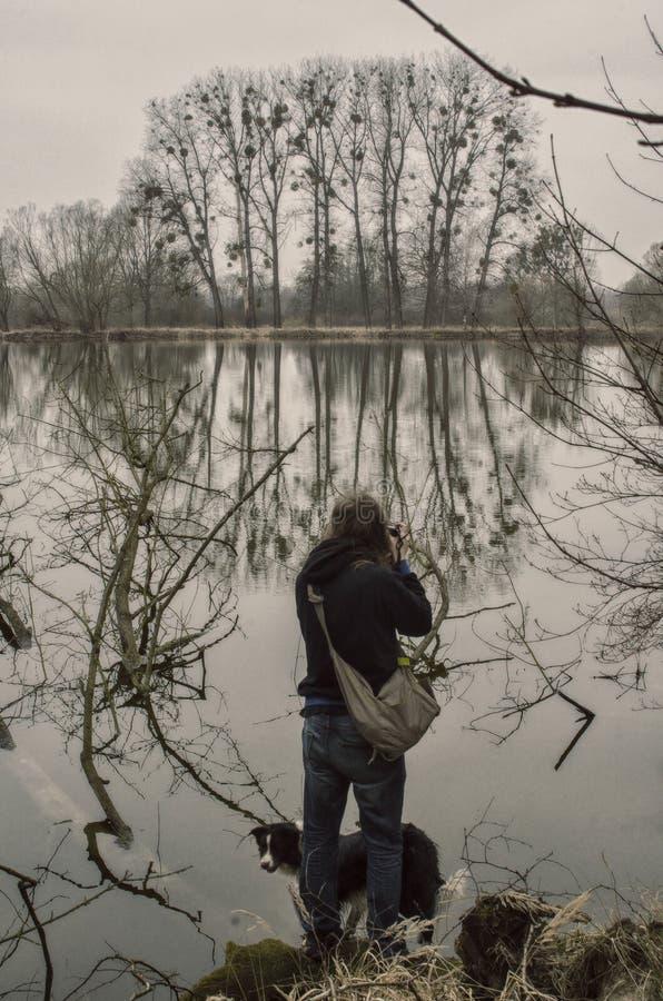 Фотограф с собакой фотографирует деревья в поверхности воды стоковое фото
