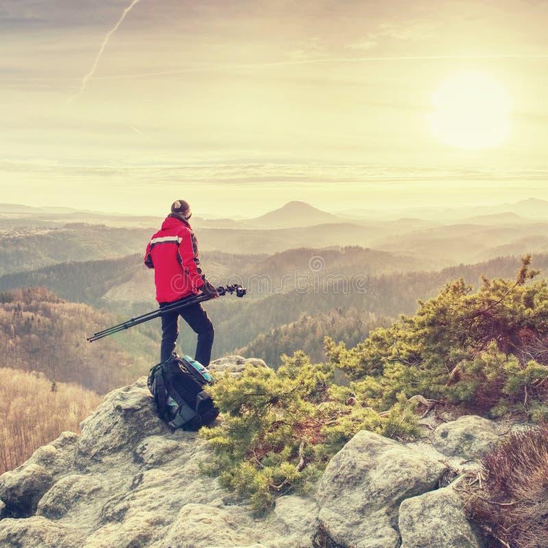 Фотограф с треногой и камера на скале и мысли стоковое изображение