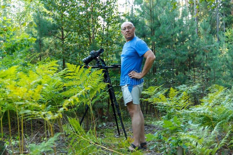 Фотограф человека с камерой на треноге приниманнсяая за стрельба в лесе стоковая фотография rf