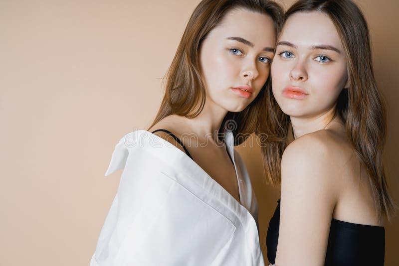 Фотомодели 2 девушки близнецов сестер красивых обнаженных смотря камеру стоковые изображения