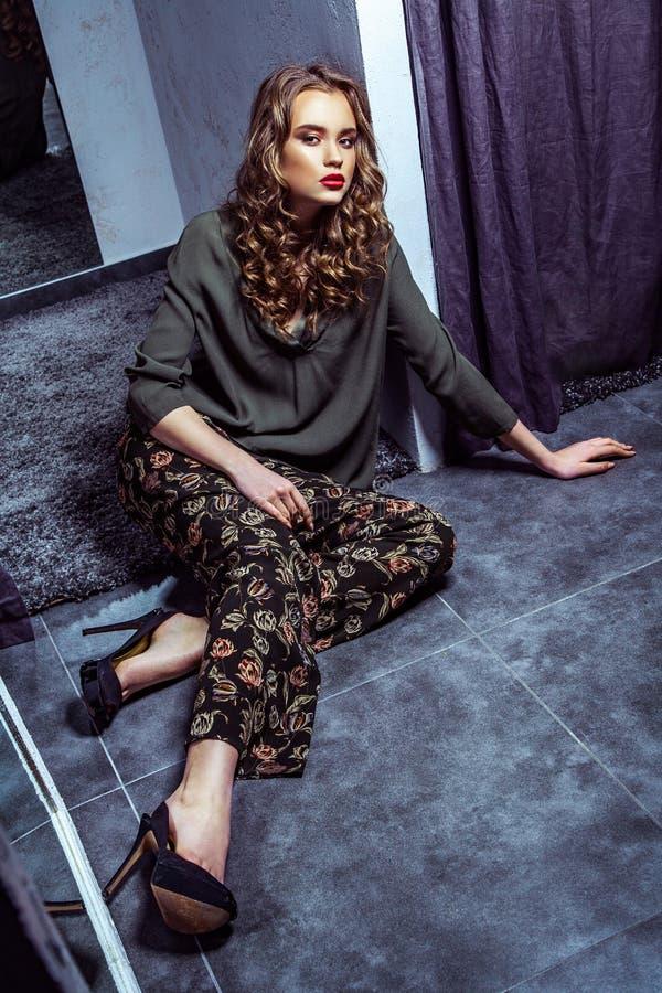 Фотомодель с макияжем и волнистый стиль причесок в стильных одеждах и ботинках высоких пяток сидя на поле в примерочной и смотрет стоковое изображение rf