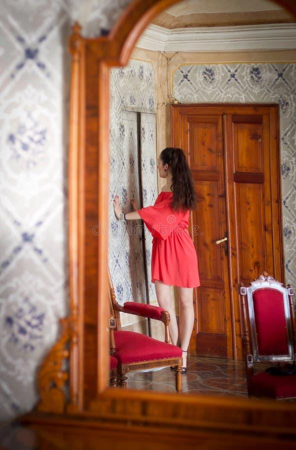 Фотомодель с платьем коралла в сатинировке отразила в зеркале стоковые изображения