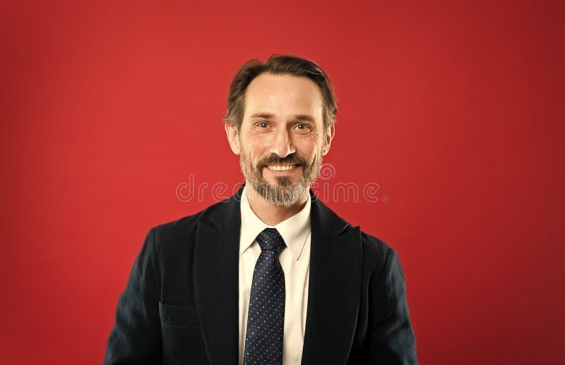 Фотомодель человека красивая зрелая нести модный костюм на красной предпосылке Костюм вдохновляет чувство доверия джентльмена стоковое изображение