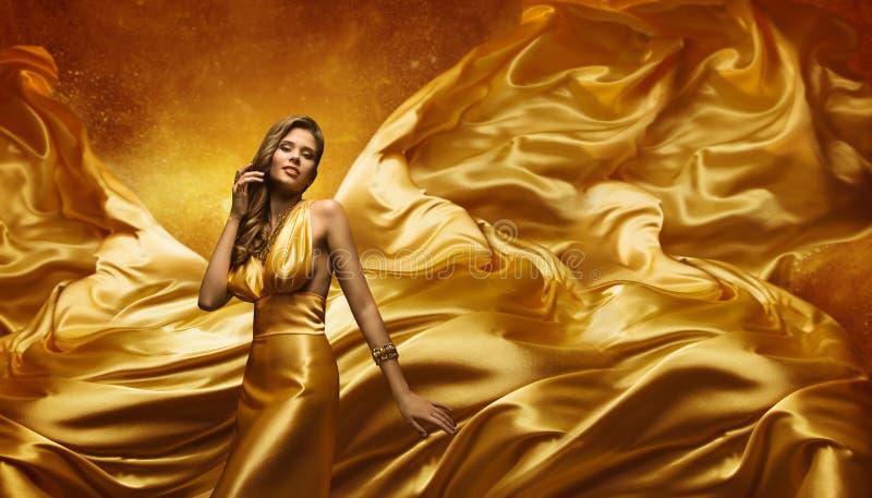 Фотомодель в платье золота, женщине красоты представляя ткань летания