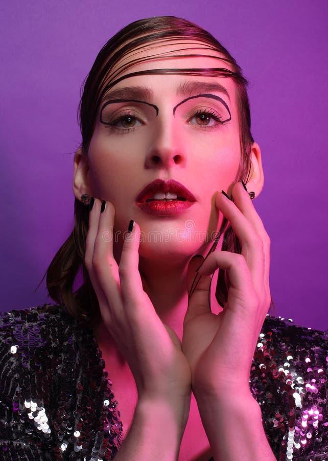 Фотомодель представляя над фиолетовой предпосылкой стоковое изображение rf