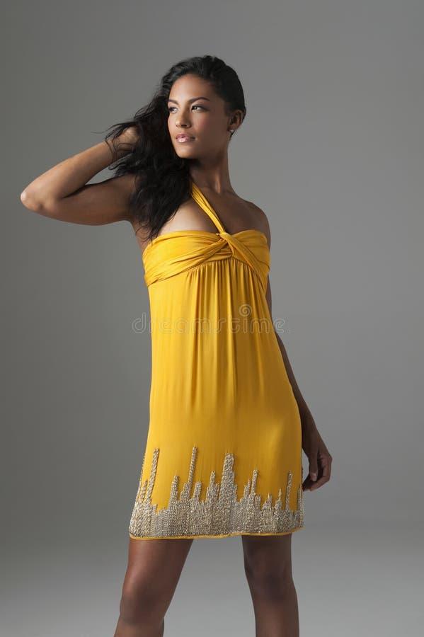 Фотомодель стоя в ярком желтом платье стоковая фотография