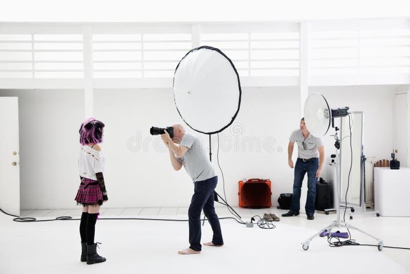 Фотомодель стрельбы фотографа в фотосессии стоковое фото rf