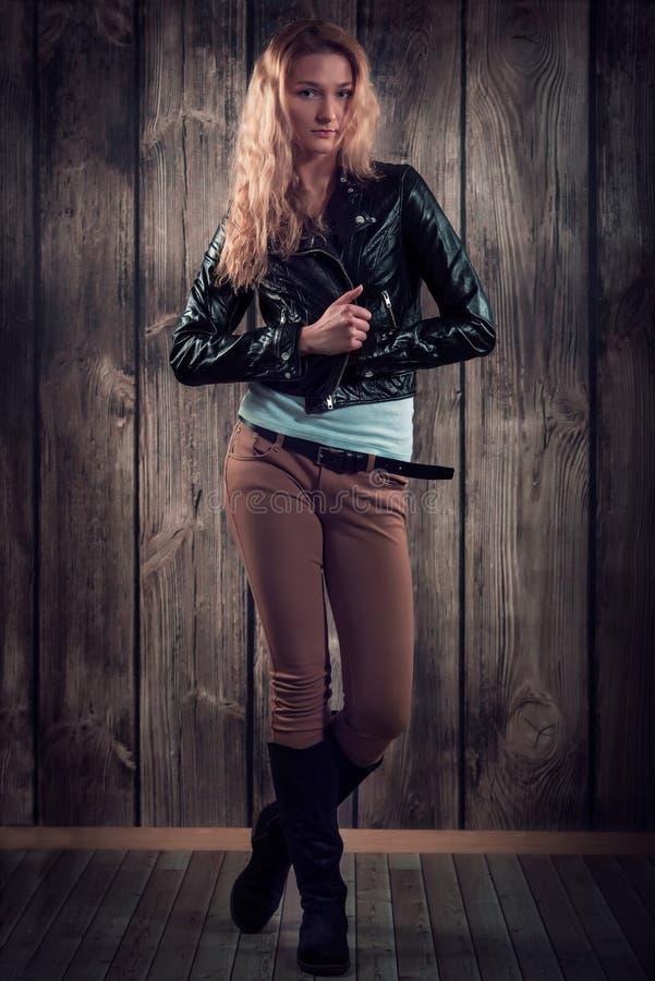Фотомодель с вьющиеся волосы одела в черной куртке, брюках джинсовой ткани и высокорослых ботинках над деревянной предпосылкой сте стоковая фотография
