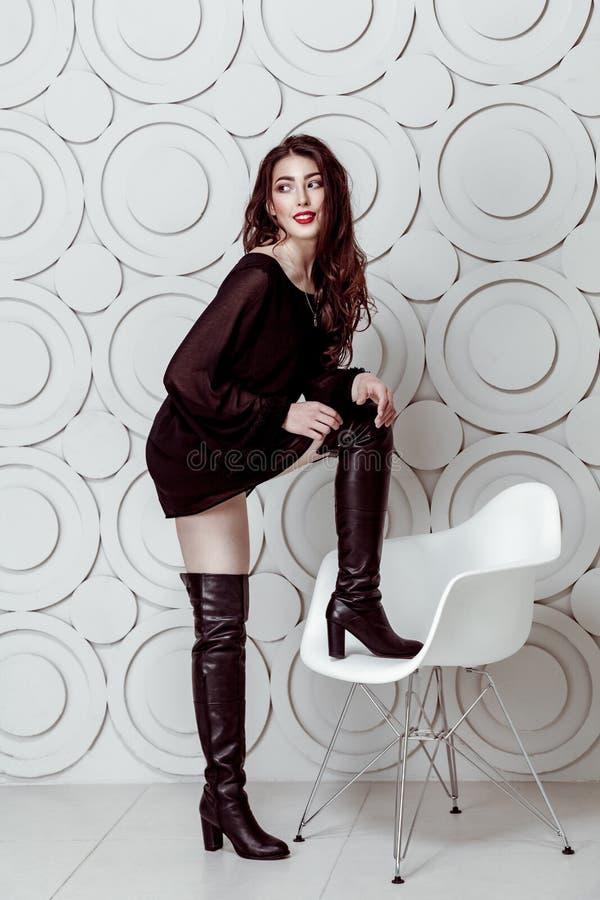 Фотомодель с составом стиля причёсок и smokey и красные губы в черном платье и ботинки представляя на белом стуле стоковые фото