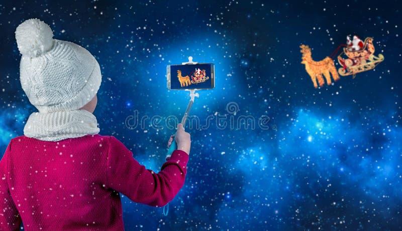 Фотоснимки мальчика Санта Клауса в санях с северным оленем который летает через небо стоковые фотографии rf