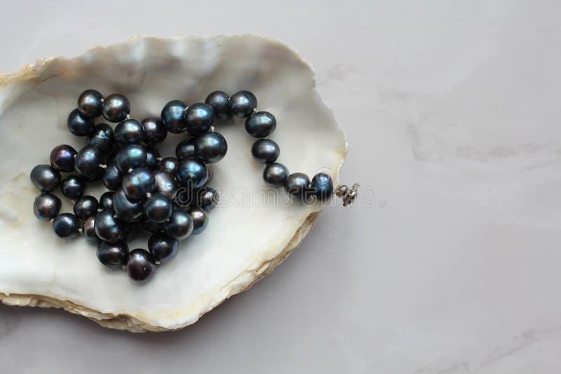 Фотоснимок макроса черных шариков жемчуга с драгоценными камнями на раковине, мраморной предпосылке стоковое фото rf