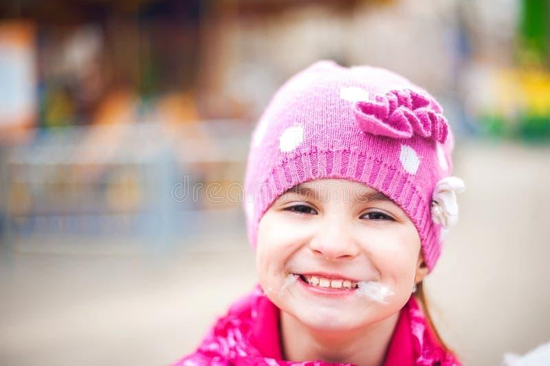 Фотоснимок остатков ` s ребенка на природе весной Девушка ребенка в яркой розовой куртке ест сладостную вату против t стоковое изображение rf
