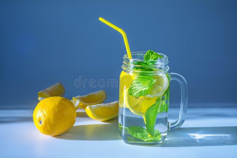 Фотоснимок прозрачной стеклянной кружки заполненной с водой, отрезанным лимоном ‹â€ ‹â€ и листьями мяты с желтой соломой стоковое изображение