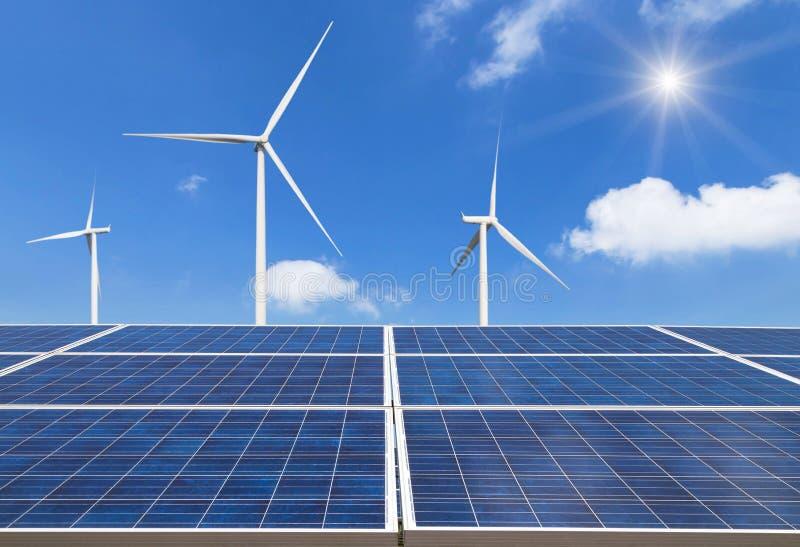 фотоэлементы photovoltaics с ветротурбинами в электростанции на голубом небе стоковое фото