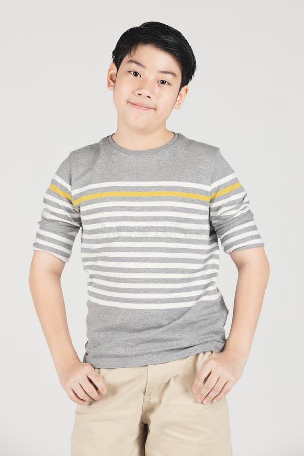 Фото азиатского молодого счастливого мальчика смотря камеру стоковая фотография rf
