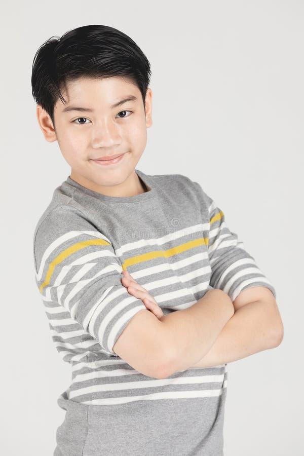 Фото азиатского молодого счастливого мальчика смотря камеру стоковые фотографии rf