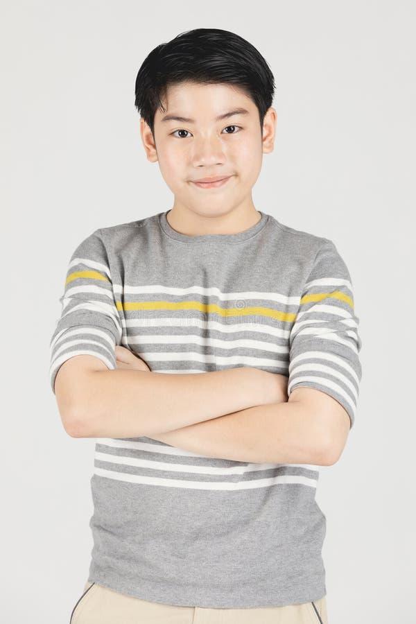 Фото азиатского молодого счастливого мальчика смотря камеру стоковые фото