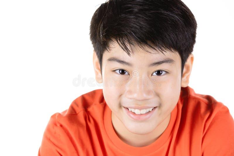 Фото азиатского молодого счастливого мальчика смотря камеру стоковое изображение