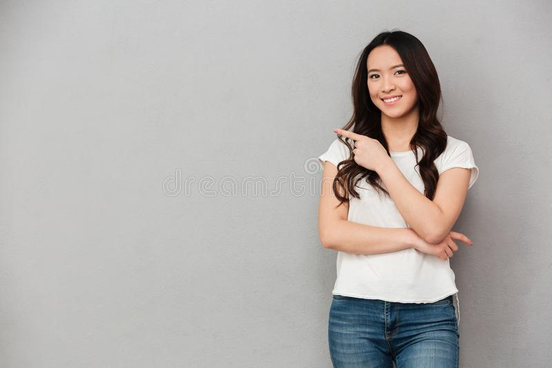 Фото азиатской приветливой женщины в вскользь представлять футболки и джинсов стоковое фото rf