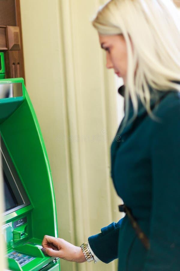 Фото блондинкы в пальто на зеленом банкомате стоковые изображения