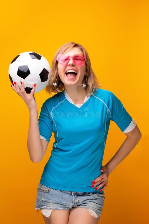 Фото блондинкы в розовых стеклах с футбольным мячом на оранжевой предпосылке стоковое изображение