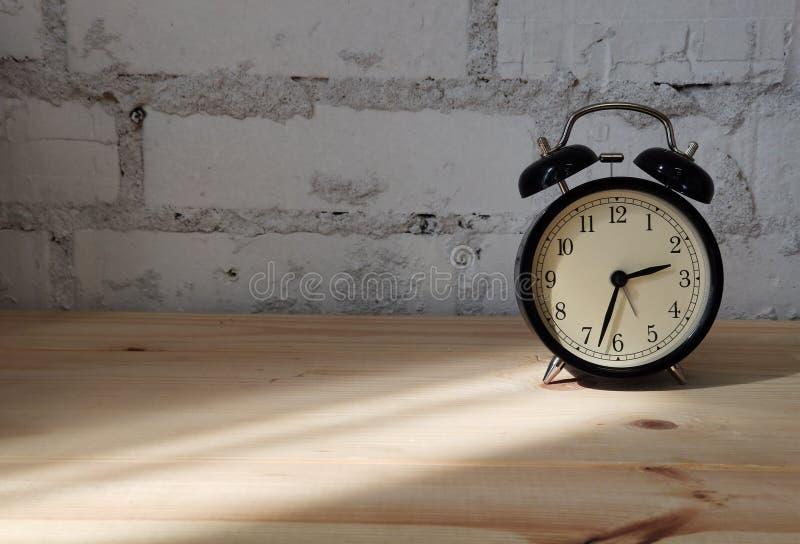 Фото будильника на деревянном столе против предпосылки кирпичной стены стоковая фотография