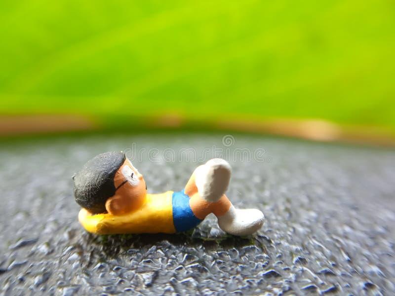 Фото, взгляд 7-ое июля 2019 уровня глаз, спать мечтающ Nobi Nobita за зелеными свежими лист, садом, Джакартой, Индонезией, съемко стоковое изображение rf
