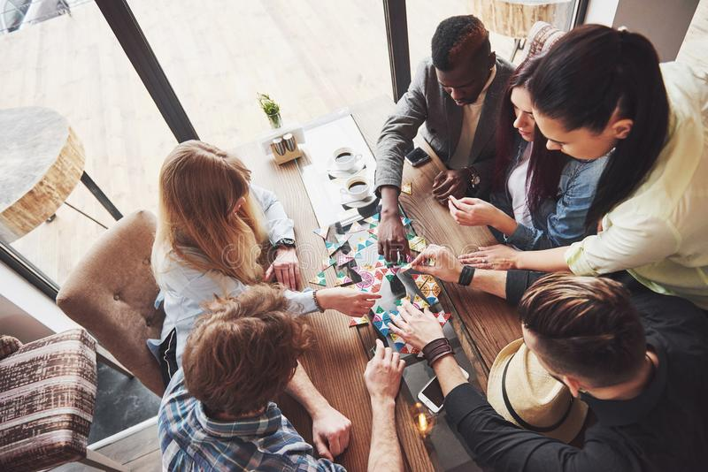 Фото взгляд сверху творческое друзей сидя на деревянном столе Друзья имея потеху пока играющ настольную игру стоковое изображение