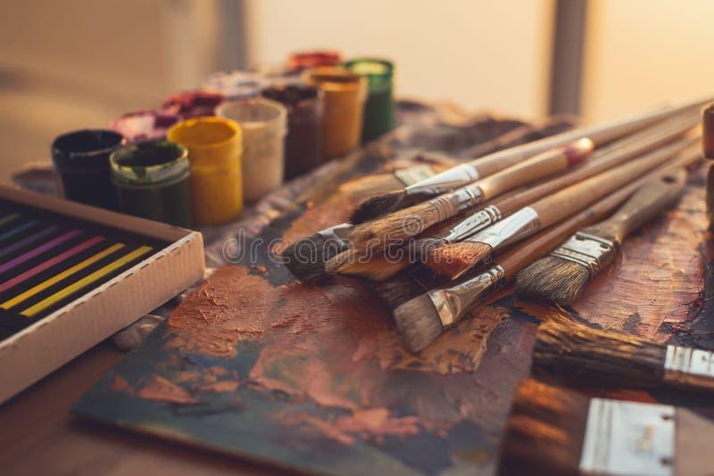 Фото взгляда угла палитры с смешанными красками масла, гуашью, crayons и paintbrushes установило в студию искусства стоковое изображение
