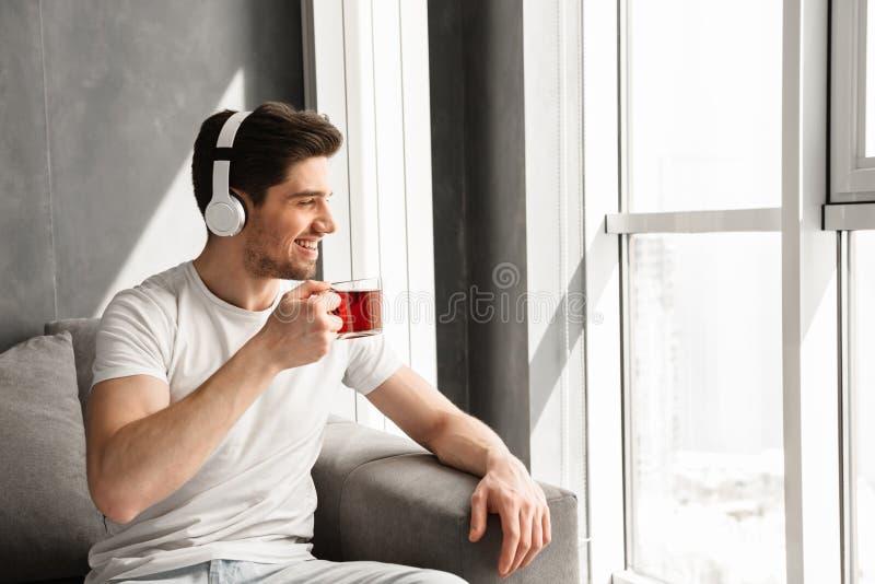 Фото внутри довольного человека смотря через окно и слушая к стоковое изображение