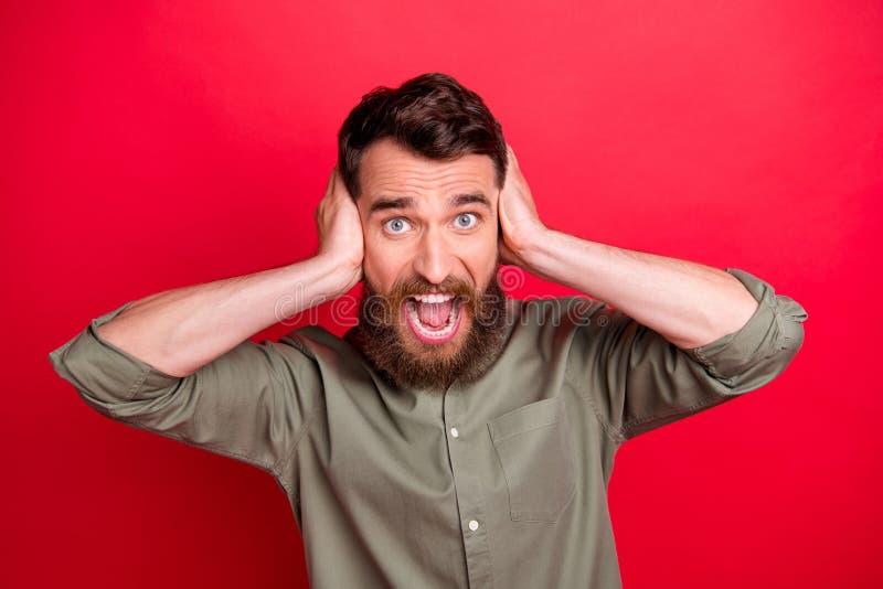 Фото вспугнутого страшить устрашенного испуганного человека кричащего в страхе пока с красной предпосылкой стоковое фото