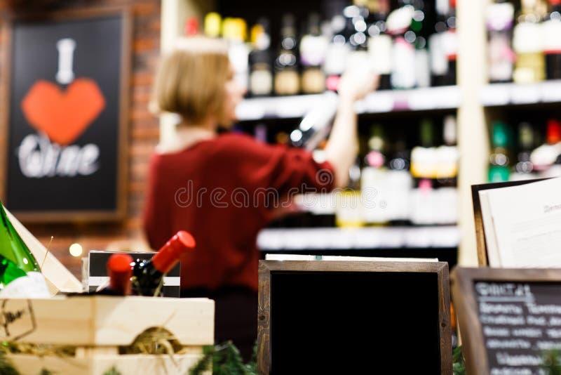 Фото деревянной коробки с вином, пустой плитой на запачканной предпосылке с женщиной стоковые фото