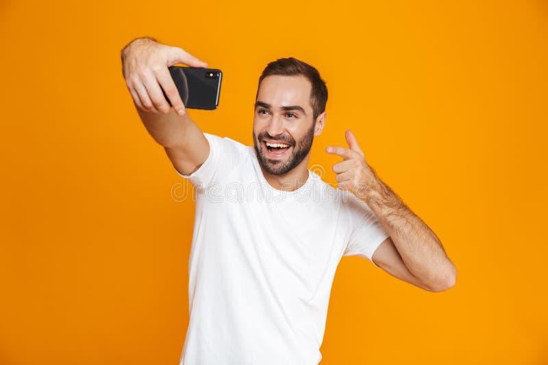 Фото довольного парня 30s в случайной носке смеясь и принимая selfie на сотовом телефоне, изолированное над желтой предпосылкой стоковая фотография rf