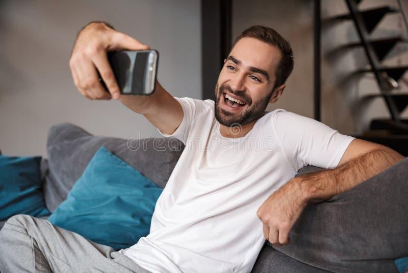 Фото довольного холостяка держа и принимая selfie на сотовом телефоне по стоковое изображение rf