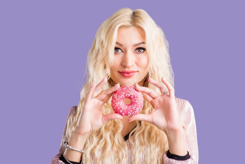 Фото женщины держит сладкий очень вкусный донут стоковое изображение