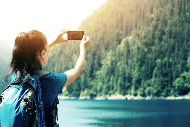 Фото женщины туристское принимая с умным телефоном стоковое изображение
