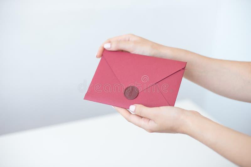 Фото конца-вверх женских рук держа серебряный конверт приглашения с уплотнением воска, подарочным купоном, открыткой, свадьбой стоковая фотография rf