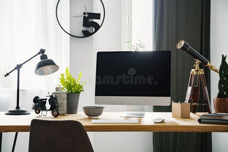 Фото конца-вверх компьютера при модель-макет стоя на деревянном столе стоковое фото