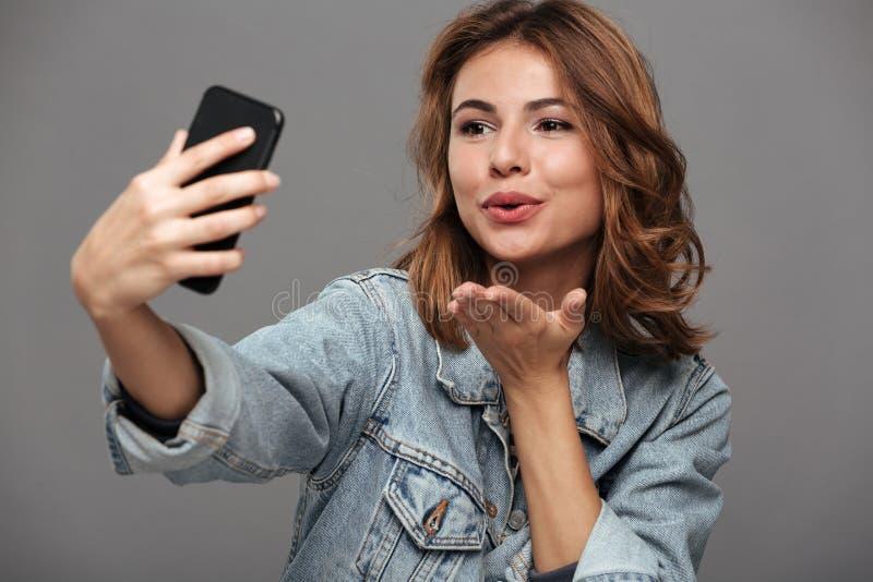 Фото конца-вверх молодой привлекательной женщины посылая поцелуй воздуха пока стоковые фото