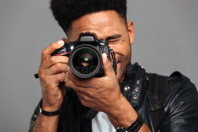 Фото конца-вверх сконцентрированного афро американского человека принимая фото дальше стоковые изображения rf